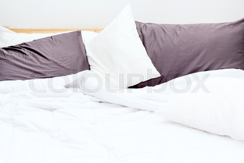 Messy bed and white bedding sheets and pillow, stock photo