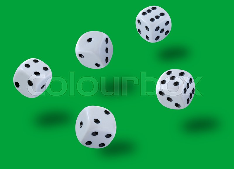 Five white dices thrown jump in a craps game, yatzee or any kind of dice game against a green background, stock photo