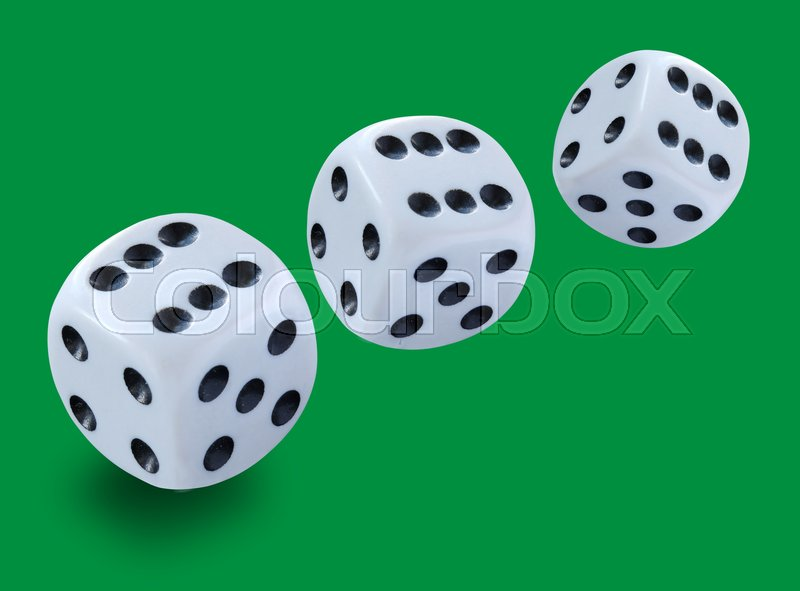 Three white dices of different size thrown in a craps game, yatzee or any kind of dice game against a green background , stock photo