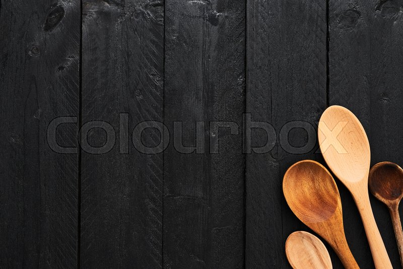 Wooden spoons on black wooden background with copy space. Top view of various types of wooden spoons on dark wooden background, stock photo