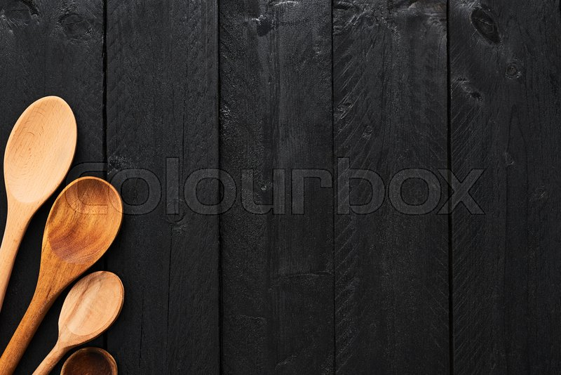 Wooden spoons on black wooden background with copy space. A collection of wooden kitchen utensils on dark wooden background. Top view, stock photo