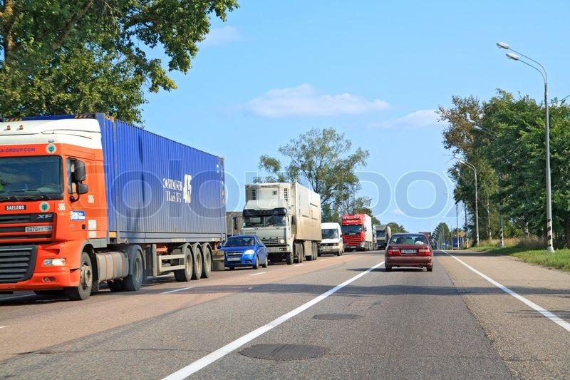 Cargo cars on asphalt road, stock photo