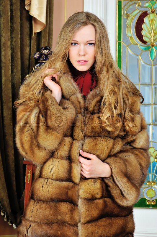 Beautiful woman in fur coat. The luxurious antique interior ...