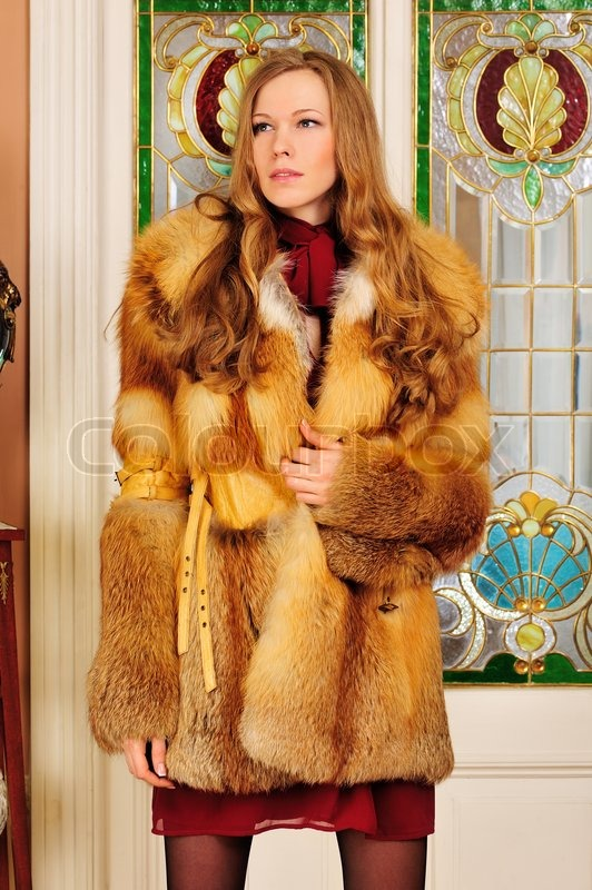 Beautiful woman in fur coat in the luxurious classical interior ...