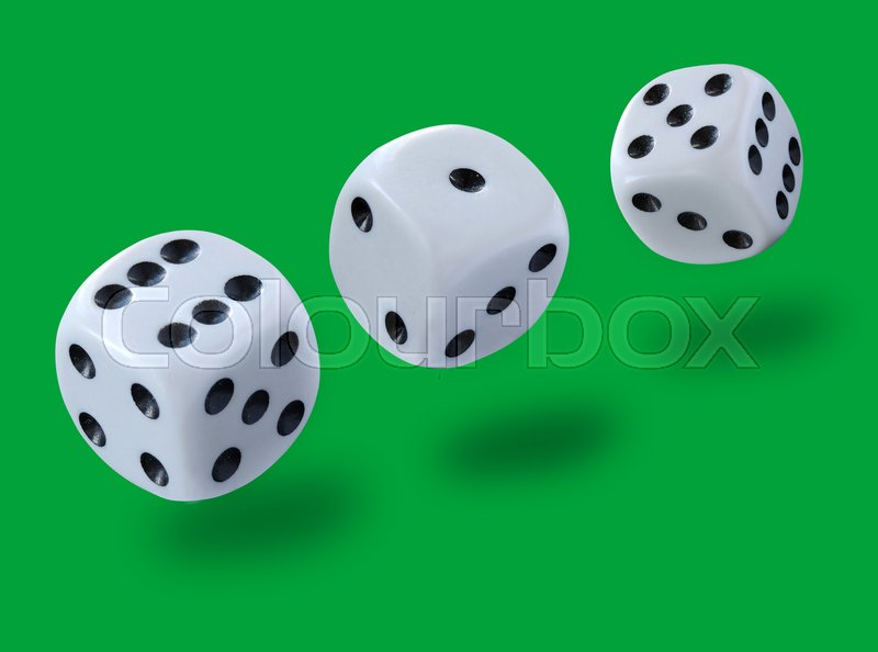 White dices thrown in a craps game, yatsy or any kind of dice game against a green background , stock photo