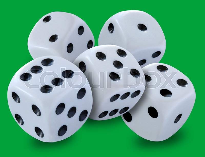 White dice in a pile thrown in a craps game, yatsy or any kind of dice game against a green background, stock photo