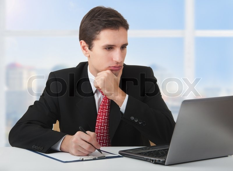 young successful business man working behind the notebook sitting