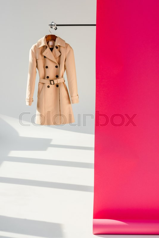 Elegant beige trench coat on hanger with pink wallpaper, stock photo