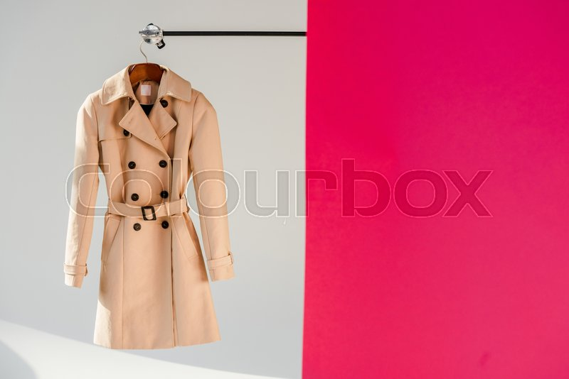 Elegant beige trench coat on hanger at pink and grey background , stock photo