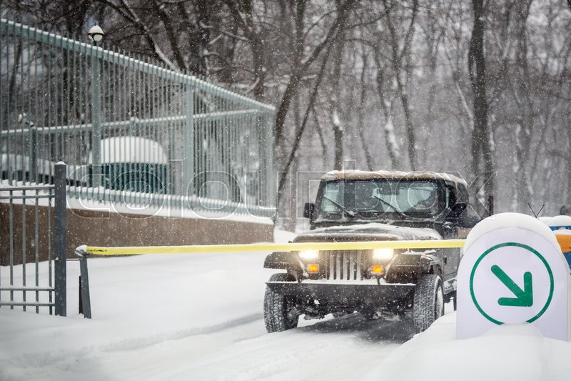 SUV car stopped at automatic entry gate during heavy snowfall. Vehicle access gateway system. Season of Blizzard at winer on city street, stock photo