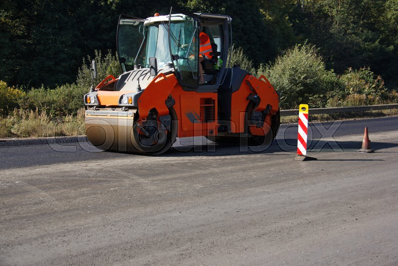 Carrying out repair works: asphalt roller stacking and pressing hot lay of asphalt. Machine repairing road, stock photo