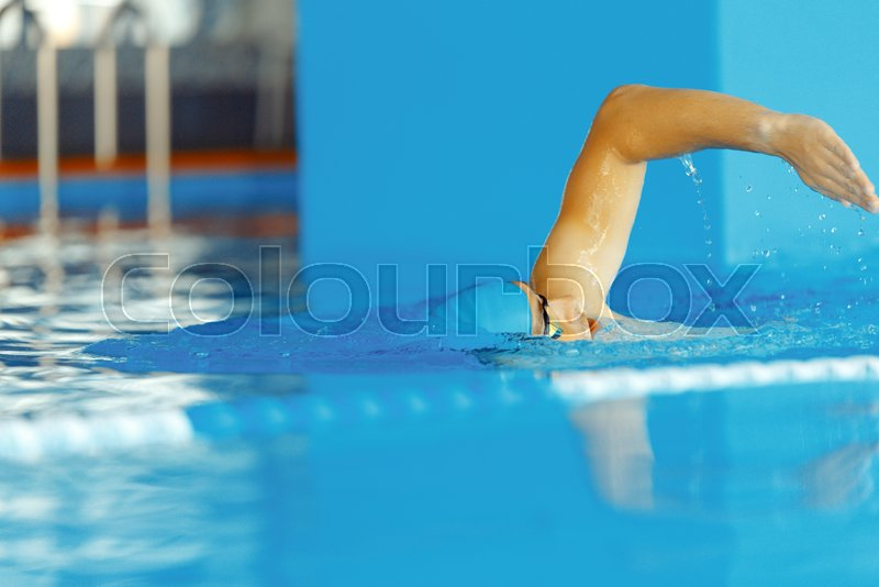 Stock image of 'Image of young athlete man in blue cap swimming in pool during workout'