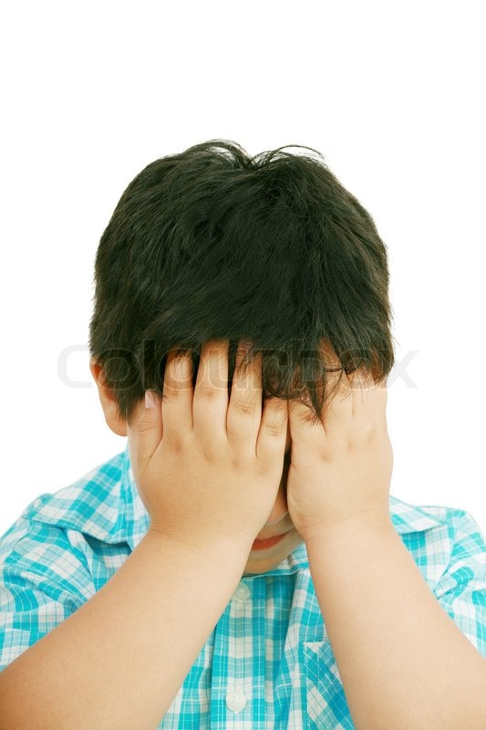 very cute little boy with sad expression and hands on face stock