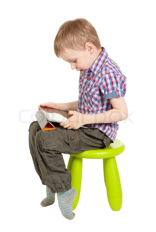 Boy with a tablet pc sitting on a green children 39 s chair for Toddler sitting chair