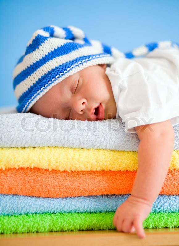 Stock image of 'Photographer's comment: This picture was created in Russia, in a small Siberian city. It was a family with 3 boys. The youngest, a two week old baby boy, was sleeping. I had a funny crocheted hat in my bag. We decided to make this little guy a bed using a stack of colorful towels.  Location: Siberia, Russia.  Equipment: Canon 5d mark II and lens Canon EF 85mm 1.8. It was a little bit dark in the bedroom, so additional flash and umbrella was used on minimal power.'
