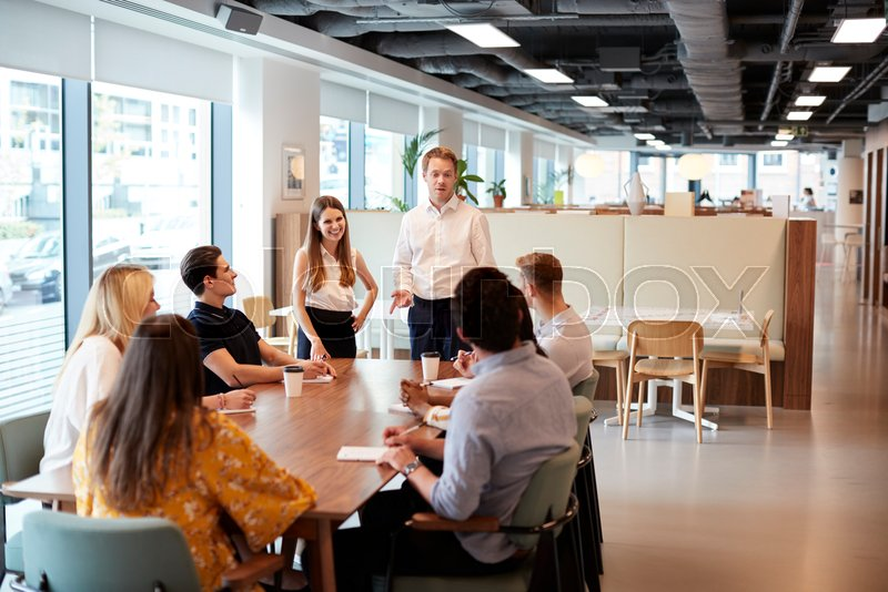 Stock image of 'Businessman And Businesswoman Addressing Group Of Young Candidates Sitting Around Table And Collaborating On Task At Graduate Recruitment Assessment Day'