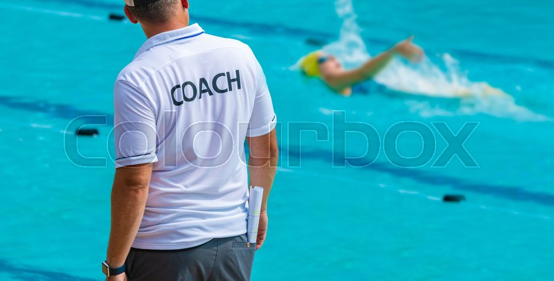 Back view of swimming coaches, wearing COACH shirt watiching his female swimmer doing backstroke at a local outdoor swimming pool, stock photo