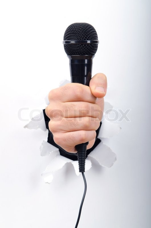 Microphone In Hand : Hand holding microphone through hole in paper stock