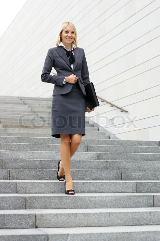 Stock image of 'Businesswoman walking down stairs'