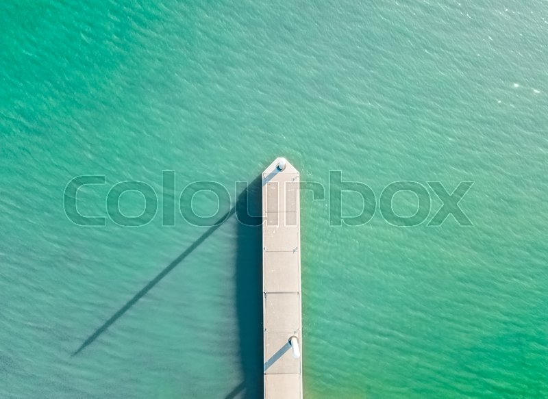 Aerial views of the little boat jetty in afternoon sunlight, its pylons casting long shadows. Copy space, stock photo