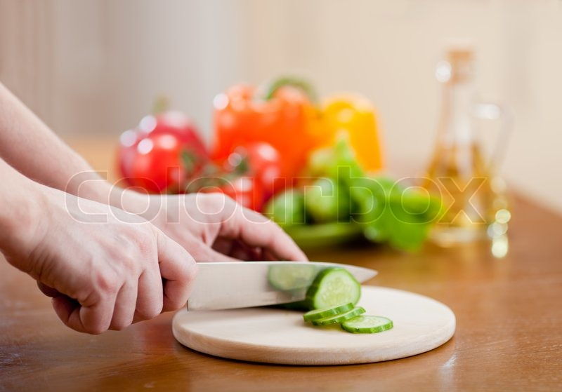Kitchen Table With Food preparing actions for vegetable salad on kitchen table focus on