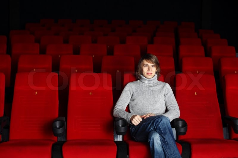 young man sitting in the cinema alone stock photo