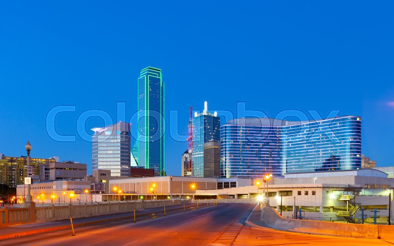 Downtown Dallas skyline at night with illuminated glass buildings seen from Houston Street, stock photo