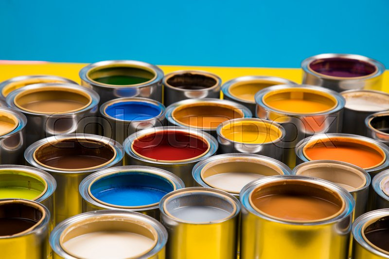 Full Buckets of rainbow colored oil paint on blue background, stock photo