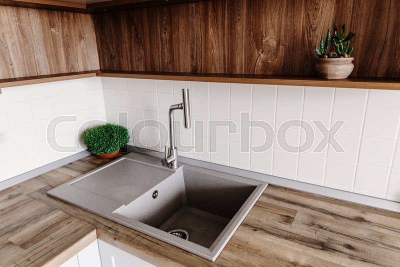 Stylish gray sink with metal faucet on modern kitchen with wooden tabletop and plants. Stylish kitchen furniture in grey color in scandinavian style. New sink, stock photo