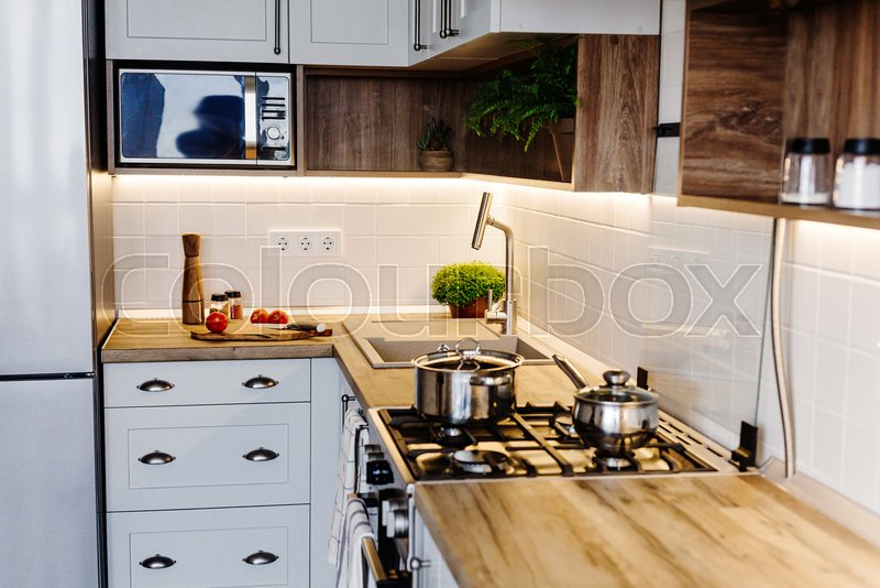 Cooking food on modern kitchen with steel oven, pots, knife on wooden cutting board with vegetables, pepper, spices,oil on wooden tabletop. Home food. Stylish ..., stock photo