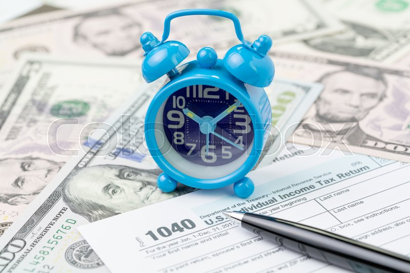 Time or deadline for yearly tax submission concept, miniature small retro alarm clock with pen on 1040 US individual income tax filling form on pile of US dollar ..., stock photo
