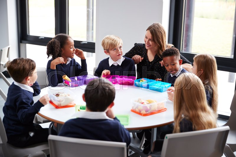 Female teacher kneeling to talk to a group of primary school kids sitting together at a round table eating their packed lunches, stock photo