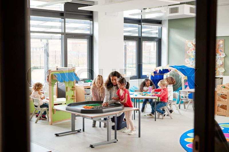 Kids playing games with a female teacher in a classroom in an infant school, seen from doorway, stock photo