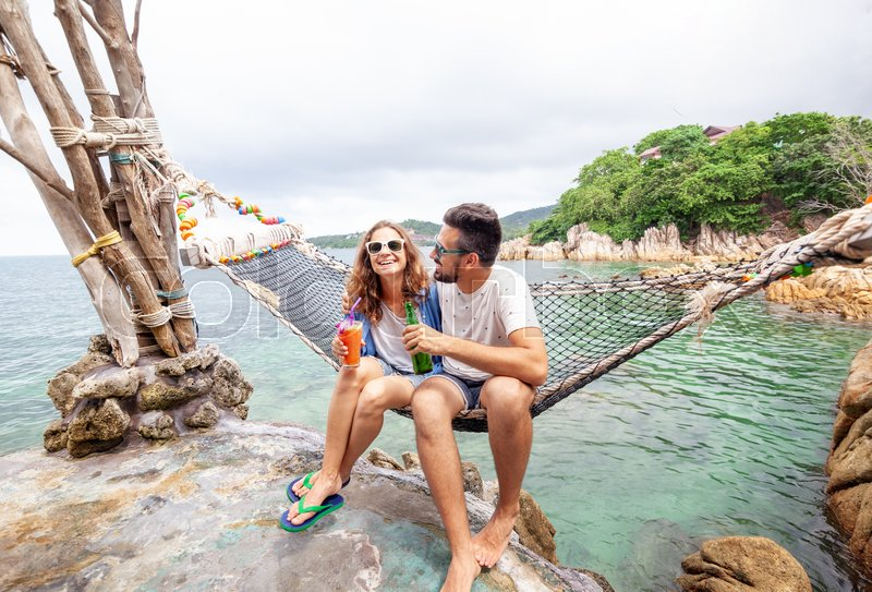Young beautiful happy smiling funny couple a man and a woman best friends on a hammock on vacation drink refreshing drinks, stock photo