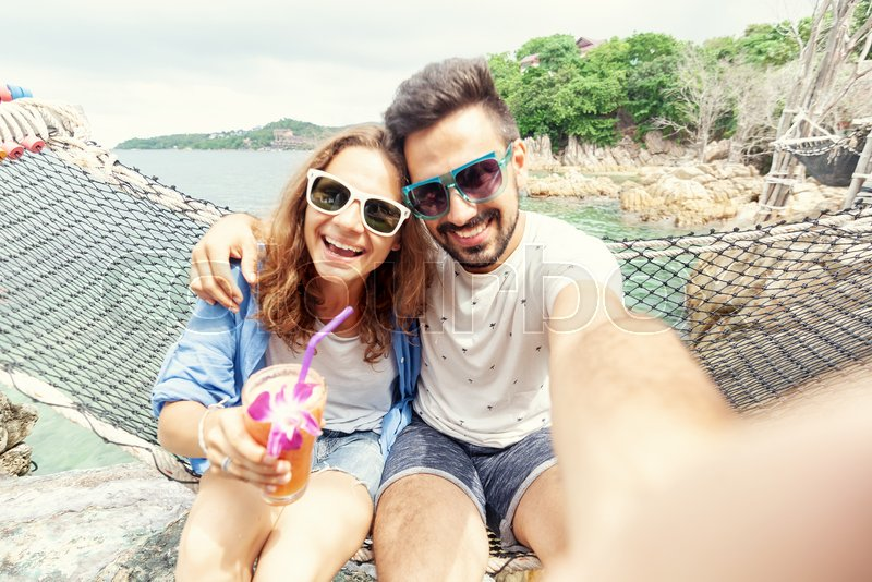 Young beautiful happy smiling funny couple man and woman best friends on a hammock on vacation makes selfie on a smartphone against the background of the sea, stock photo
