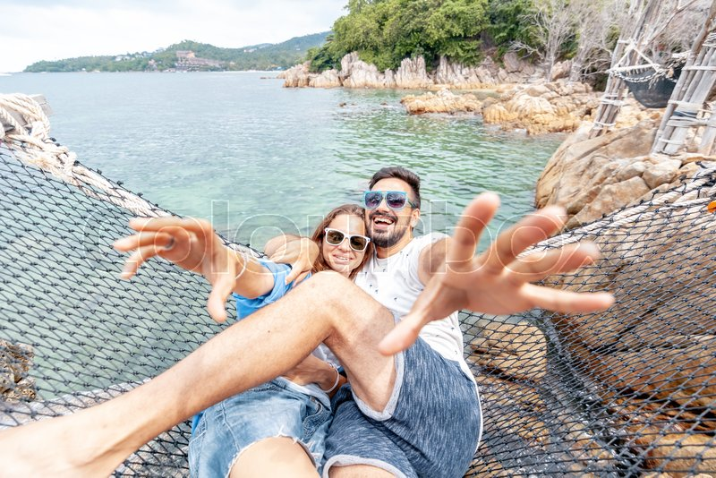 Young beautiful happy smiling funny couple man and woman best friends on a hammock on vacation chat and enjoy life, stock photo