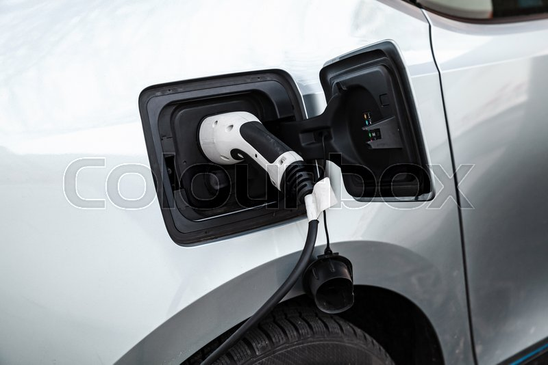 Electric car charging with cable on a parking lot, stock photo