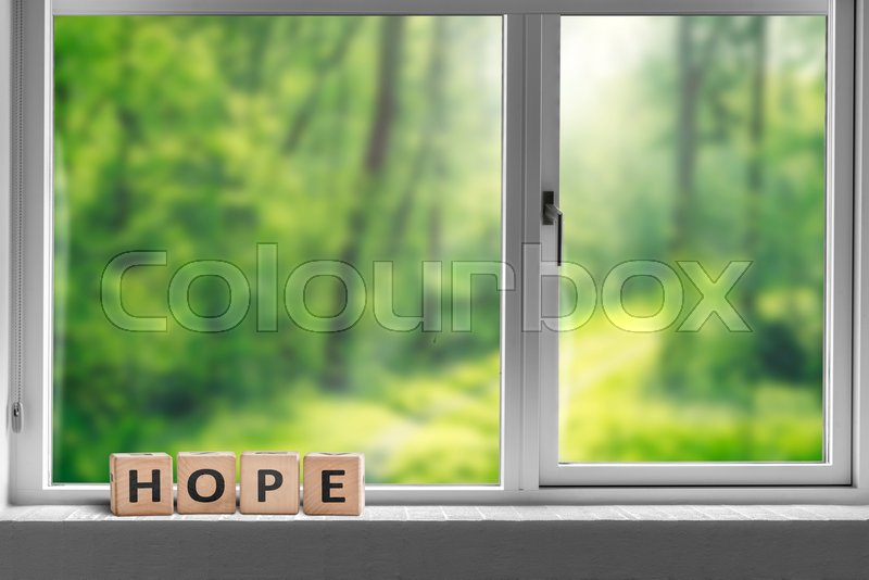 Hope sign in a window sill with a view to a green forest in sunlight, stock photo