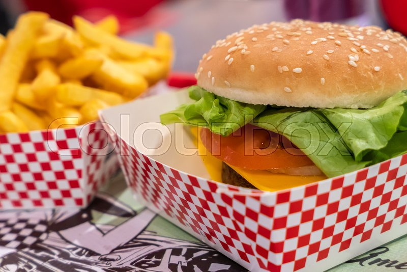 Prepared vegan seitan burger meal. On defocused blurry background the chips fries. Ideal for concepts of alternative lifestyle, stock photo