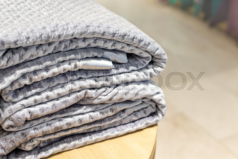 Folded velour blanket on wooden table at store, stock photo