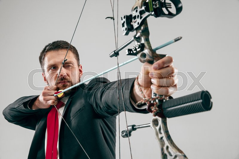 Businessman aiming at target with bow and arrow, isolated on gray studio background. The business, goal, challenge, competition, achievement concept, stock photo