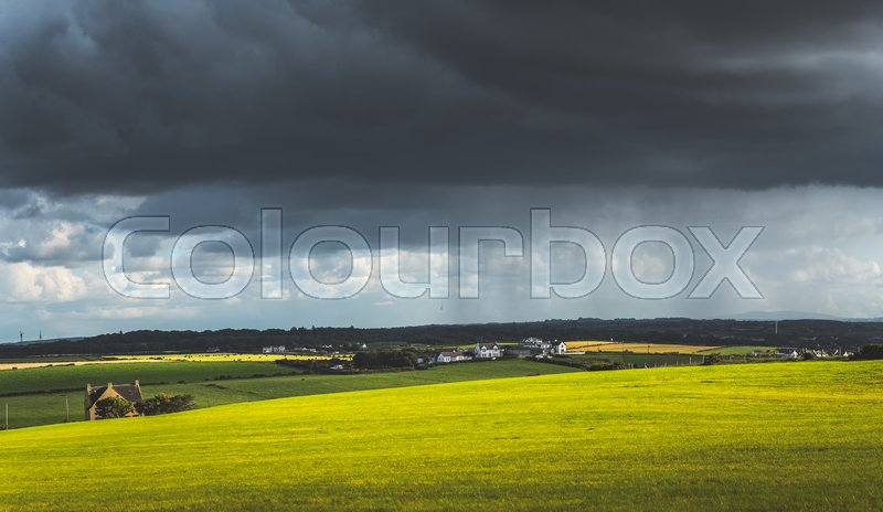 Grey rainy sky above the green meadow. Northern Ireland landscape. Dense dark clouds under the grassland and village. Stunning countryside Irish scenery. Horizon ..., stock photo