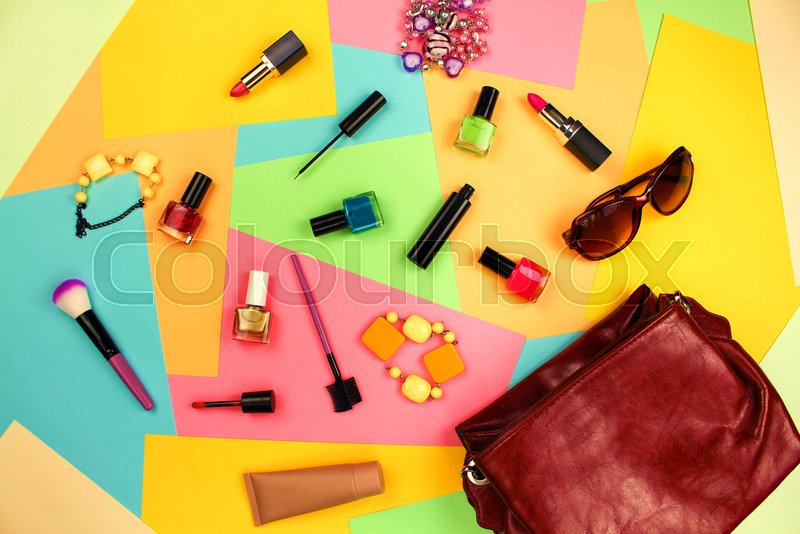 Things from open lady purse. Cosmetics and women\'s accessories fell out of red handbag on colourful background. Top view. Flat lay, stock photo