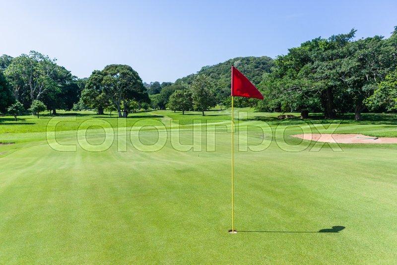Golf course hole flagstick green scenic summer coastal course, stock photo