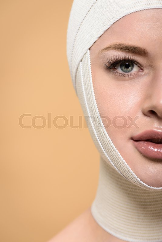 Half face of young woman with bandages over head looking at camera isolated on beige, stock photo