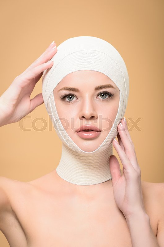 Naked young woman touching bandages over head and looking at camera isolated on beige, stock photo