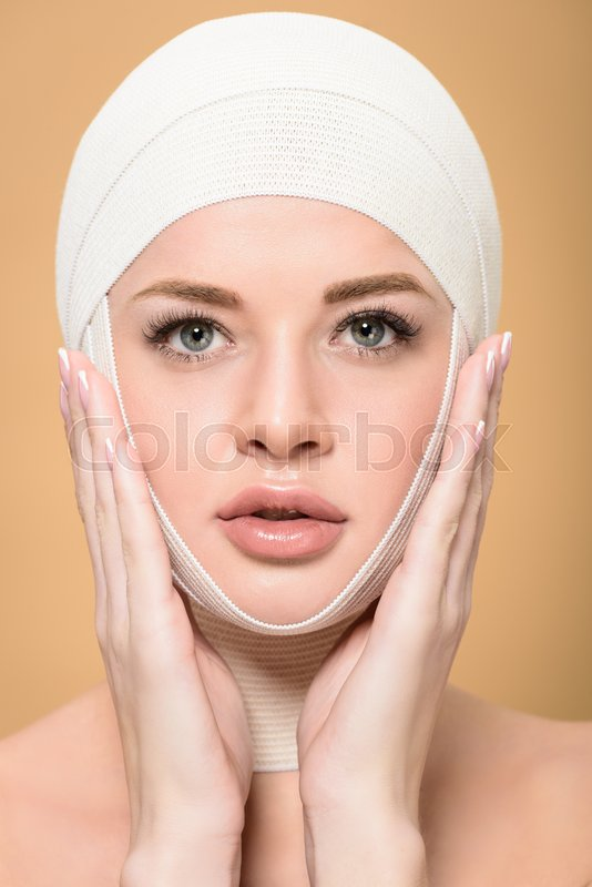 Woman with bandages over head touching face and looking at camera isolated on beige, stock photo