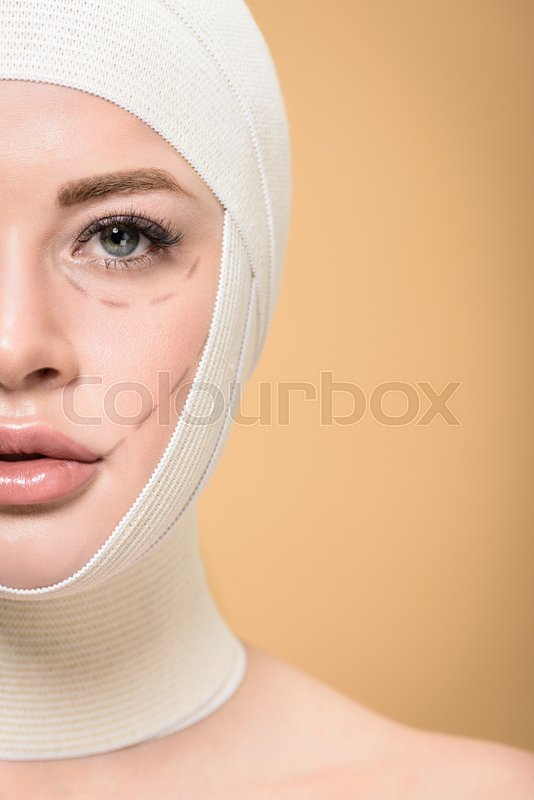 Cropped shot of woman with bandages over head and correcting marks on face looking at camera isolated on beige, stock photo
