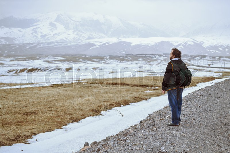 Touris wearing backpack and standing at the rural road while looking at the winter mountains, stock photo