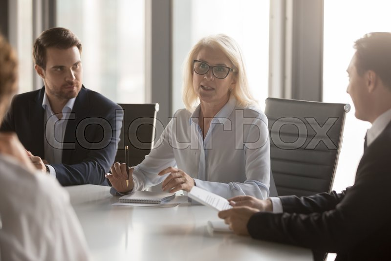 Serious middle aged businesswoman talks at group board executive meeting, confident mature old female leader speaking discussing work offers solution negotiating ..., stock photo